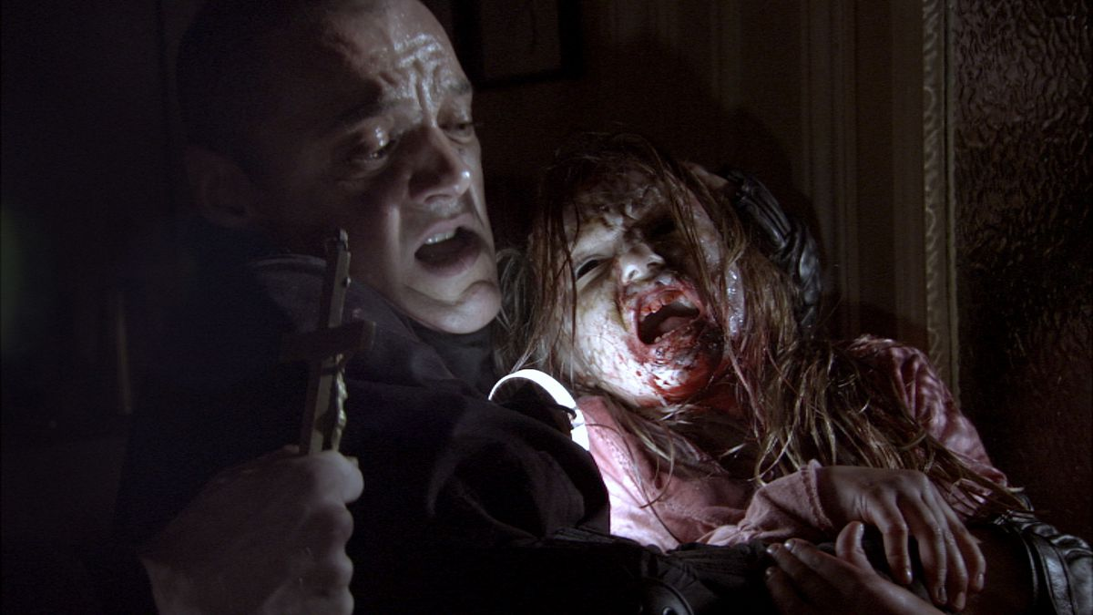 A frightened-looking man clutching a crucifix slumps against the base of a door, holding a small girl in pink who's covered in blood, has all-black eyes, and appears to be screaming.