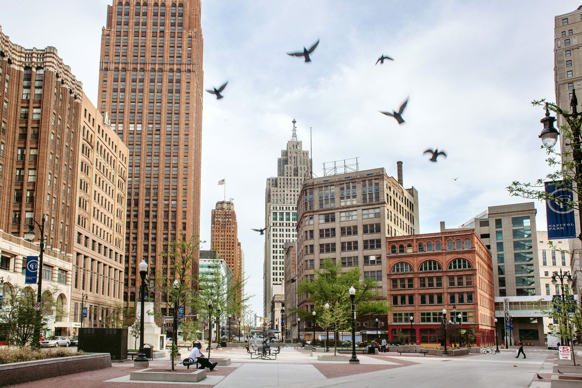 Pigeons fly over the historic Capitol Park in downtown Detroit.