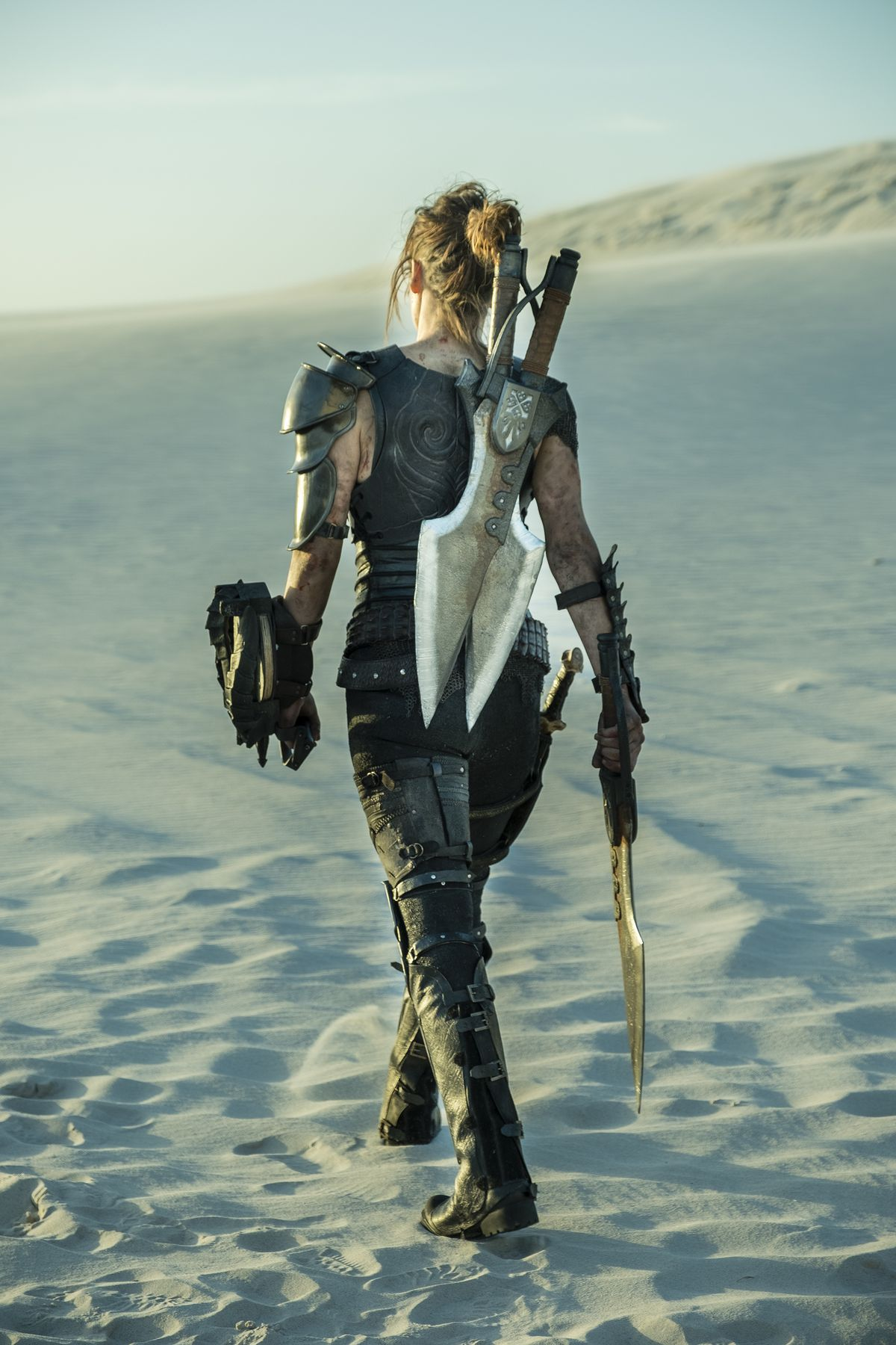 Milla Jovovich with back to camera walks through the desert with her Monster Hunter blades dangling on her back