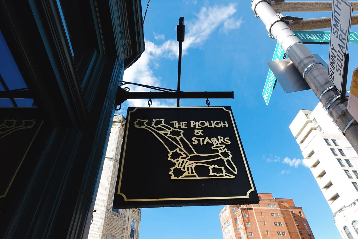 Looking up at a bar sign from almost underneath it. It's a dark rectangle with light print that says Plough and Stars with a line drawing of a plough and stars.