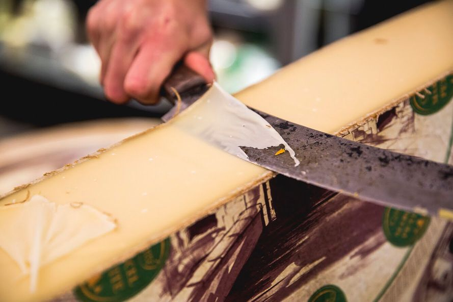 Slicing French Comté cheese at Provisions cheese shop, wine bar and deli on Holloway Road, one of the best places to eat cheese in London