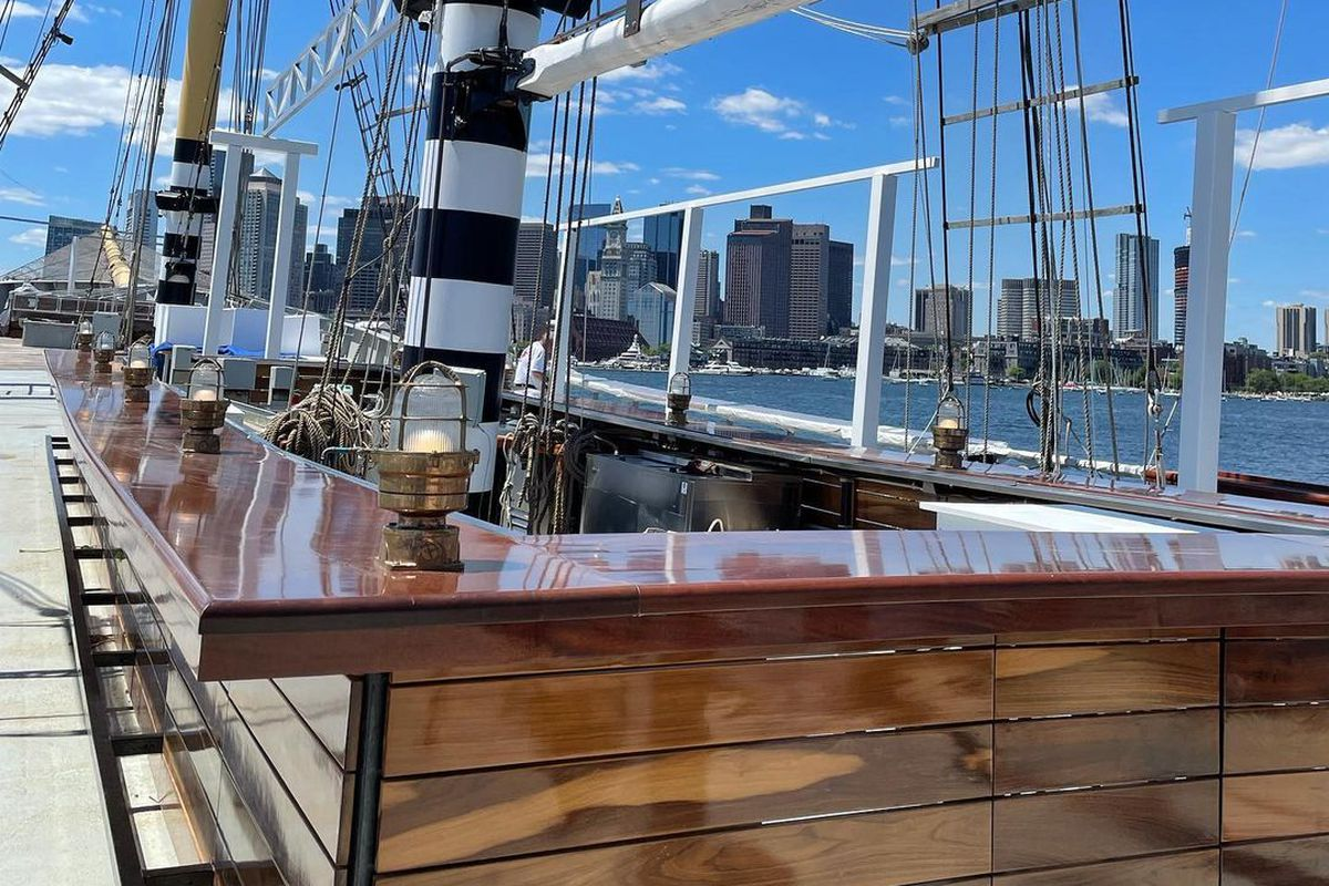 A bar is built into a tall ship on the water on a sunny day