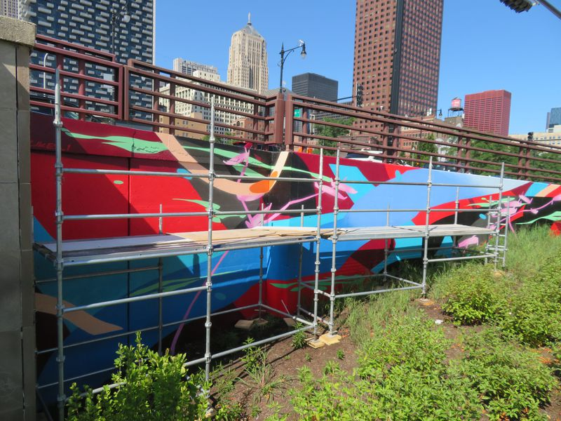 An abstract painting of red, blue, black, pink, and green cover the side of a road embankment. There's scaffolding in front.