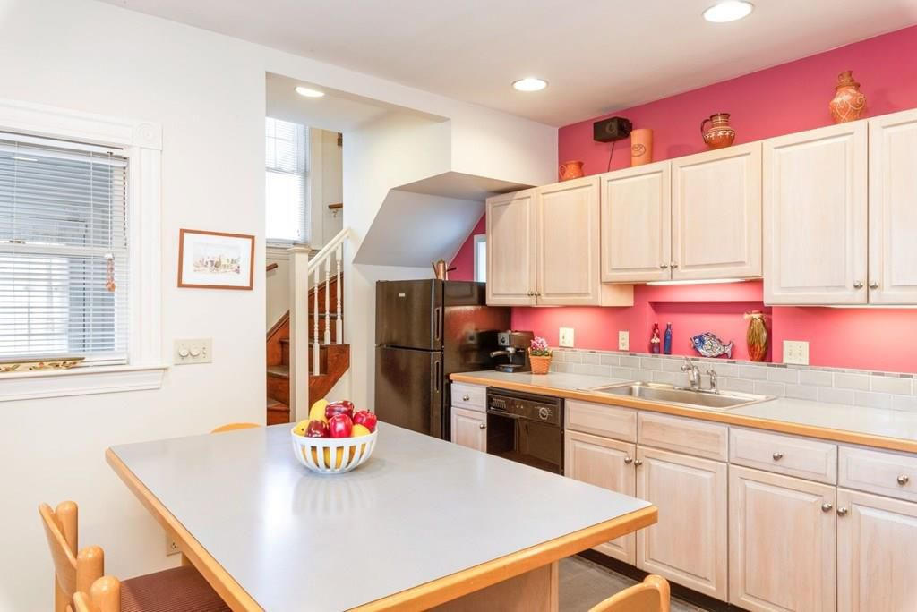 A snug kitchen with cabinetry and a table and chairs.