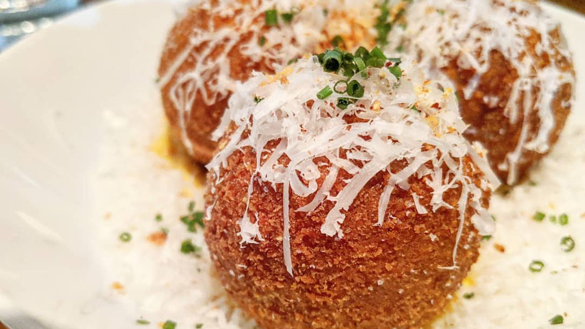 Three big balls of arancini sit on a plate, topped with grated cheese, orange zest, and herbs.
