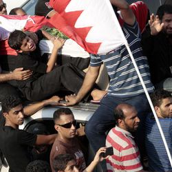 The casket carrying Ali Hussein Niema, 17, who allegedly was shot dead by riot police late Friday, is accompanied by his father, Hussein, seated holding a picture of his son on the front of the vehicle, and his younger brothers, crying beside the father and seated second left on vehicle, during a politically charged funeral procession attended by thousands in Sadad, Bahrain, on Saturday, Sept. 29, 2012. The death could bring fresh protests by Shiite-led groups seeking a greater political voice in the Sunni-ruled Gulf kingdom.