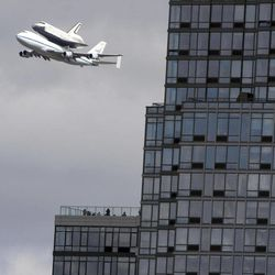 People watch from the balcony of a building as the space shuttle Enterprise, riding on the back of the NASA 747 Shuttle Carrier Aircraft, cruises over the Hudson river,  Friday, April 27, 2012 in New York. Enterprise is eventually going to make its new home in New York City at the Intrepid Sea, Air and Space Museum.
