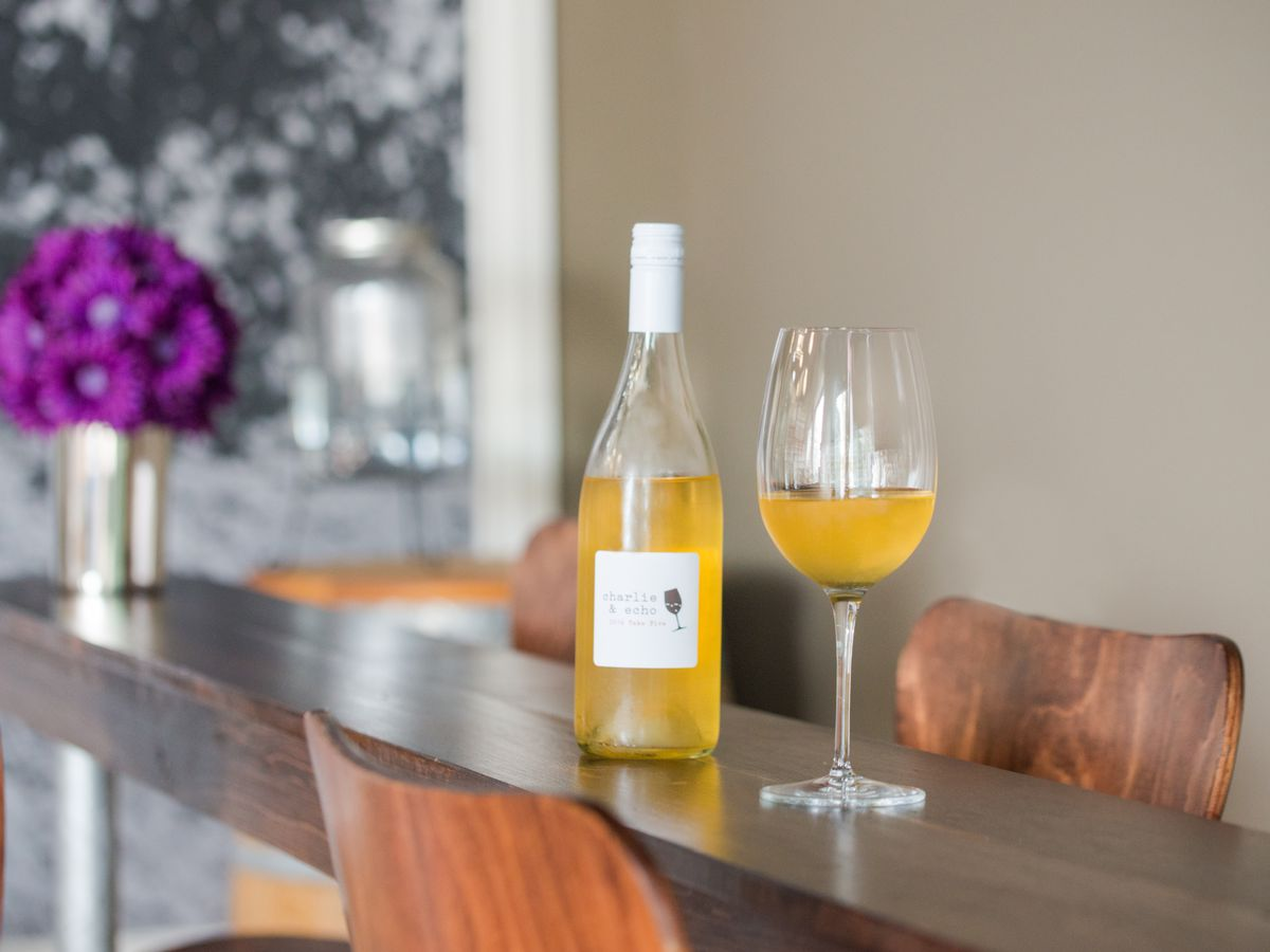 Bottle of wine and filled wine glass on a wooden table.