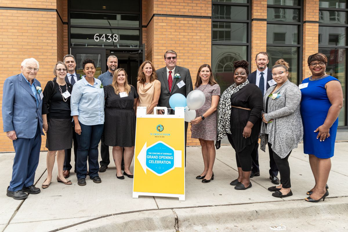 """13 men and women stand in a row in front of a brick storefront and behind a sing reading """"The Concord at Sheridan grand opening celebration."""""""