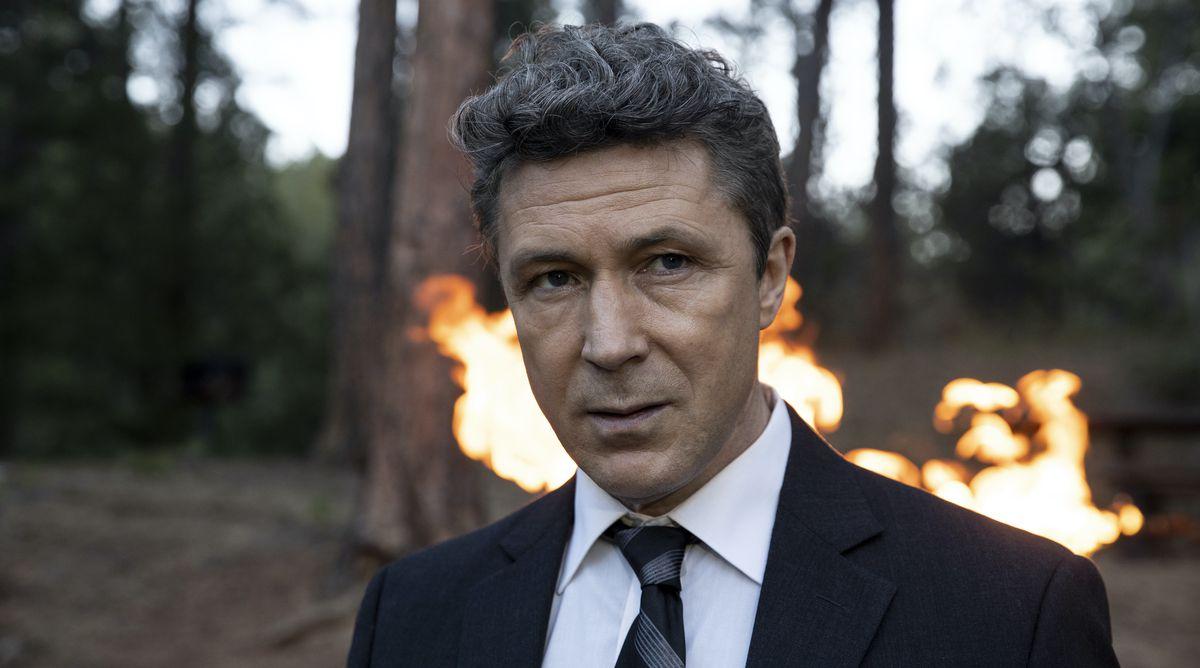 Aidan Gillen en el bosque con un fuego detrás de él en Los que me desean muerto