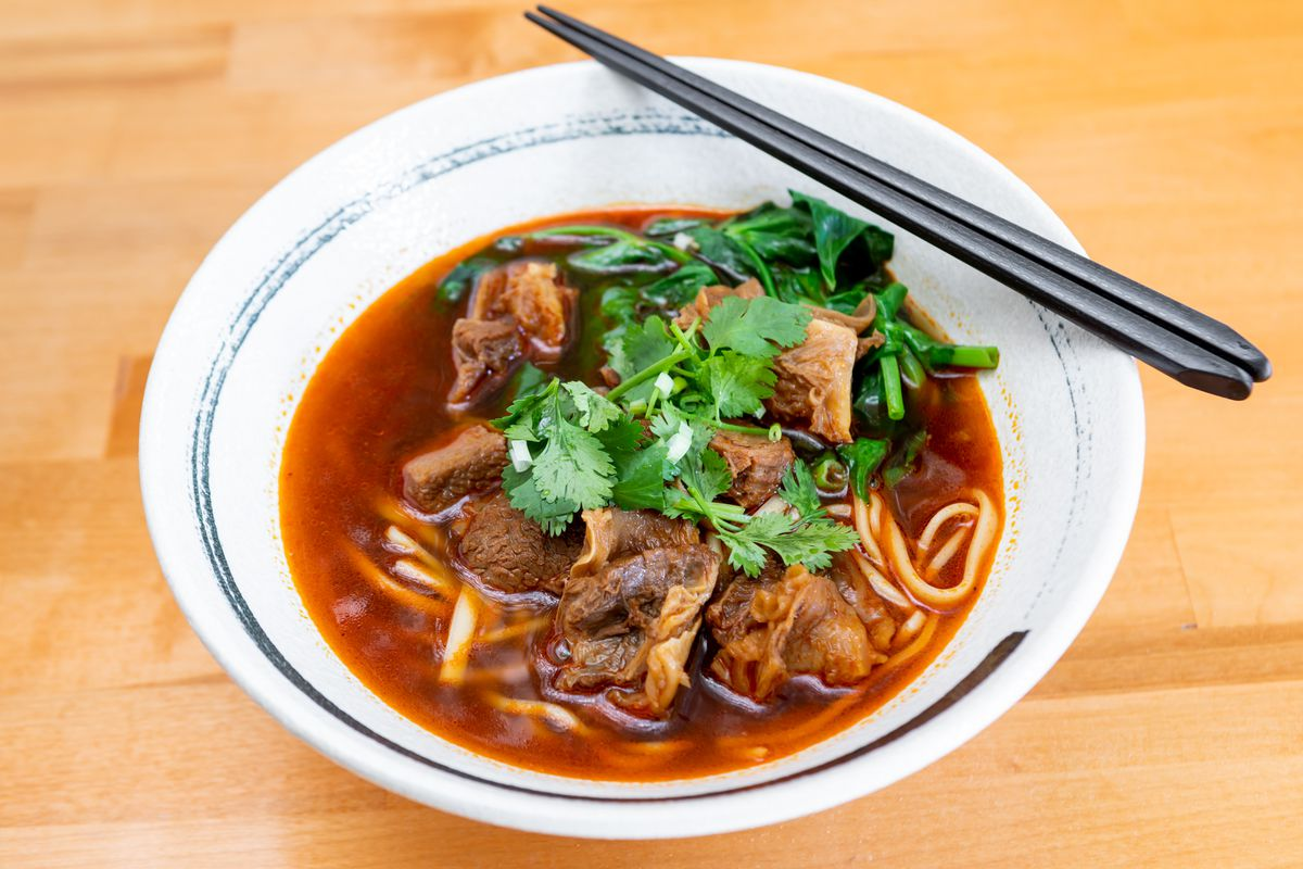 A bowl of beef noodle soup, with large chunks of stew meat, topped with fresh cilantro