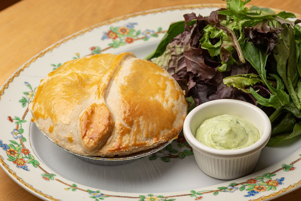 Brazilian chicken pot pie on a shabby chic plate with green lettuce and side of dressing.