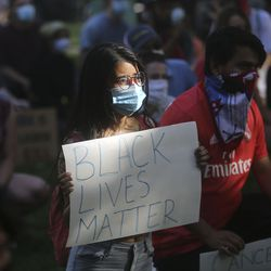 """Sanskriti Timseena holds a """"Black Lives Matter"""" sign and listens to speakers at a Party for Socialism and Liberation rally outside of the Salt Lake City-County Building on Monday, June 1, 2020."""