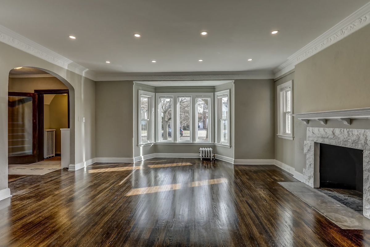 A big living room with hardwood floors. There's a stone fireplace, bay windows, and recessed lighting on the white ceiling.