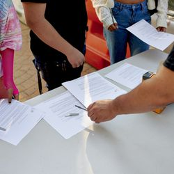 Students receive their COVID screening forms from a faculty member on the first day of school.