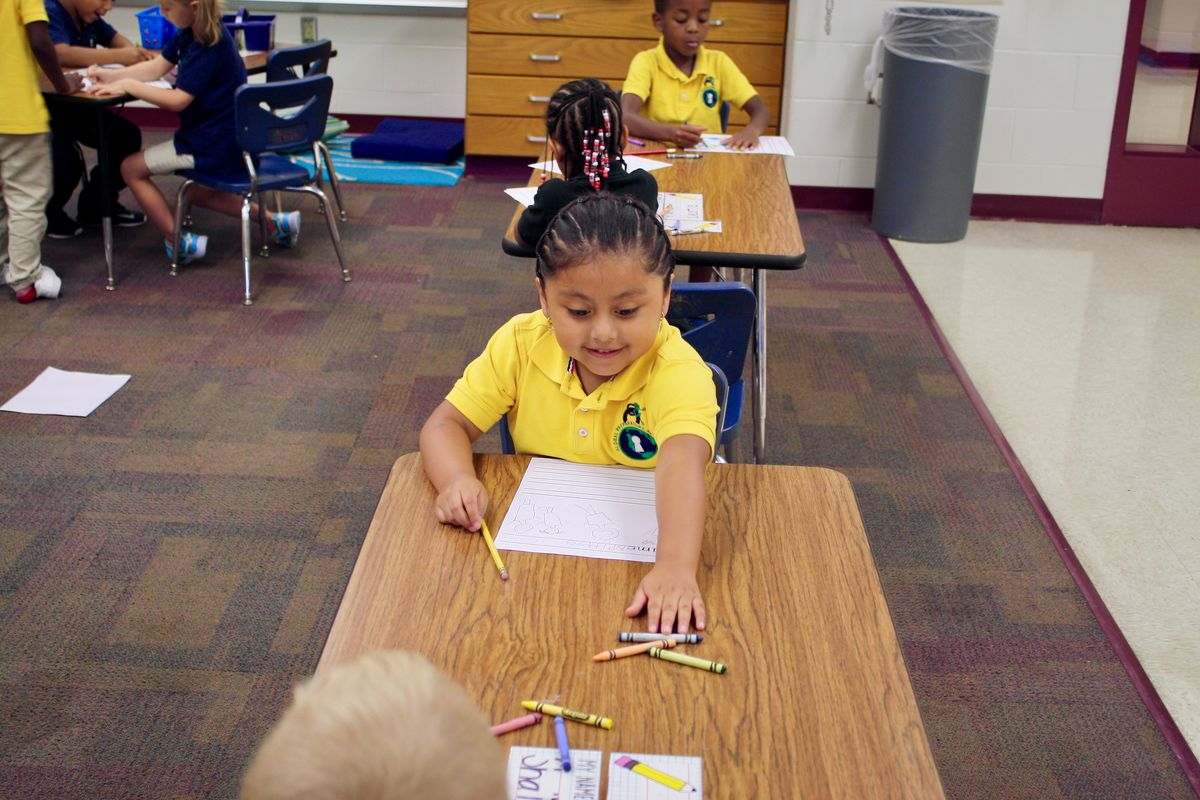 A kindergarten student reaches for crayons during a lesson at Global Prep Academy. The school has a Spanish dual language program for grades K-2.
