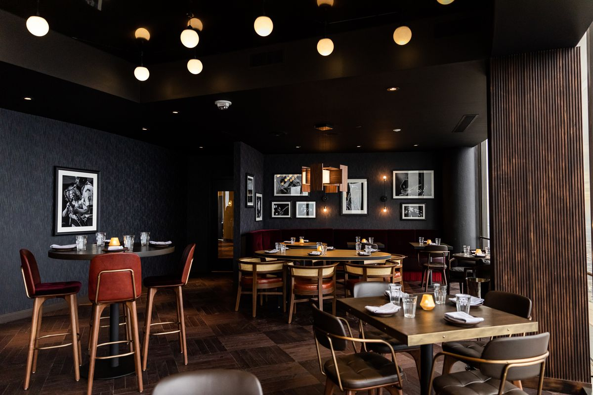 Black patterned wallpaper lines the walls surrounded by red velvet banquettes and wood tables at Hearth 71.