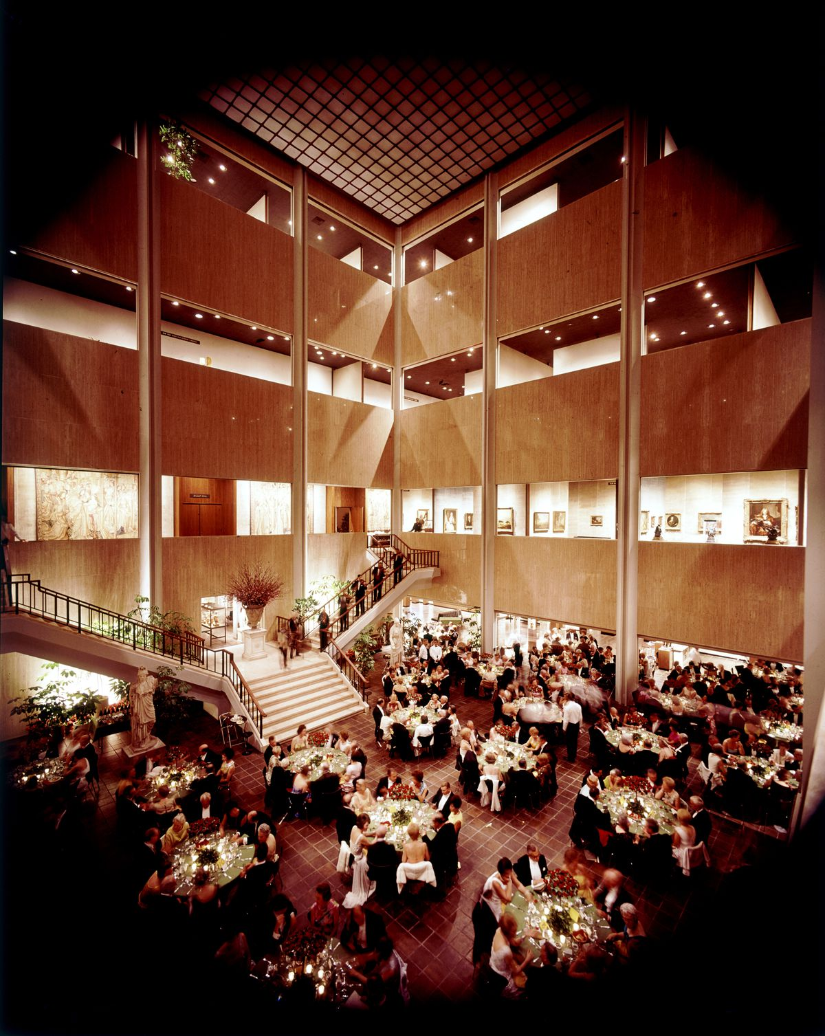 An interior shot of a banquet in a large atrium with super tall ceilings.