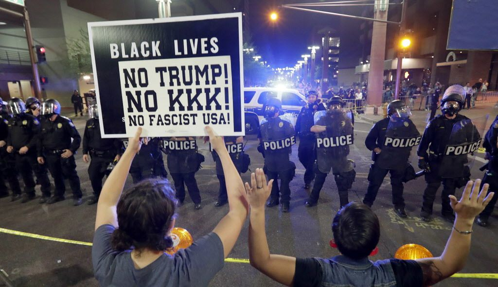 Protesters raise their hands after Phoenix Police used tear gas outside the Phoenix Convention Center.   Matt York/AP