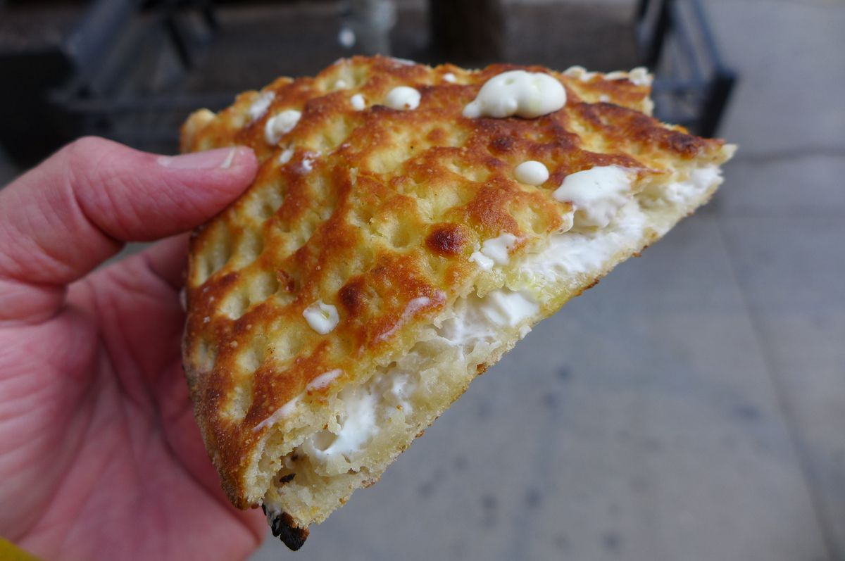 A hand holds a floppy slice of focaccia with white cheese oozing on the top and sides.