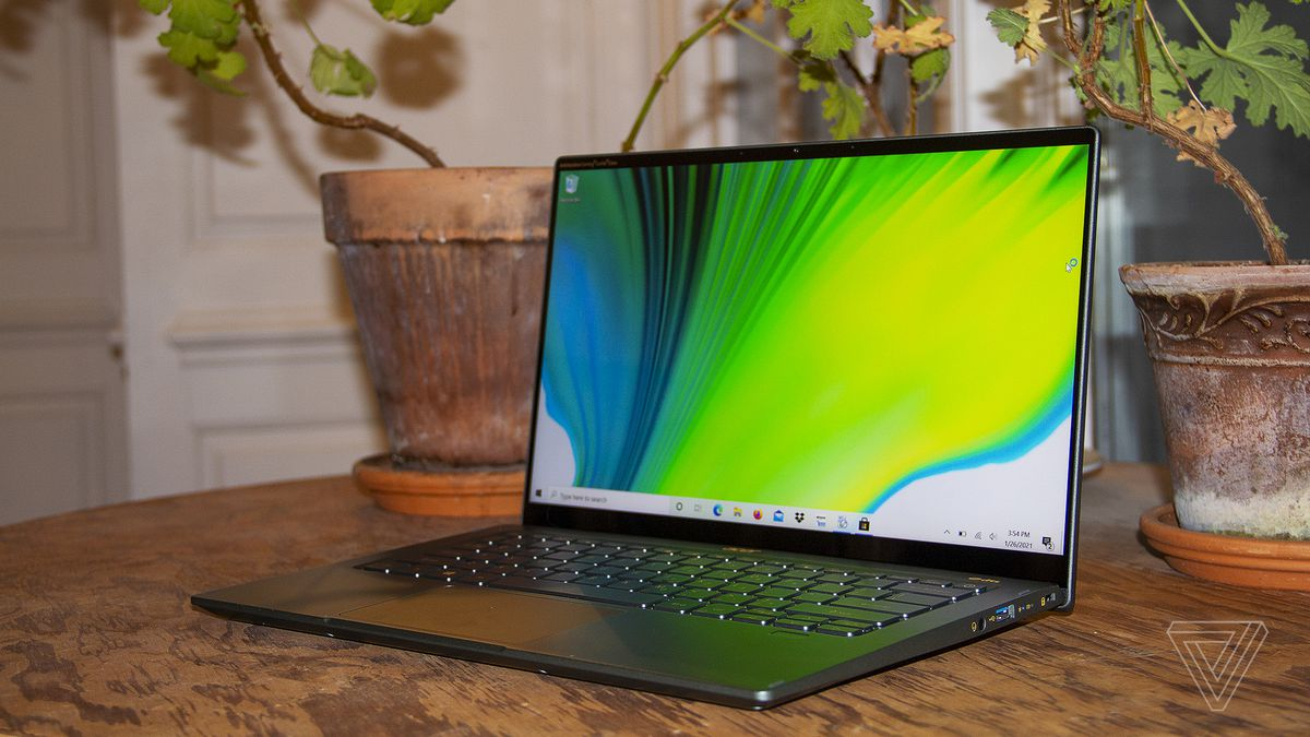 The Acer Swift 5 on a table in front of two house plants, open and angled to the left. The screen displays a green, blue, and white background.
