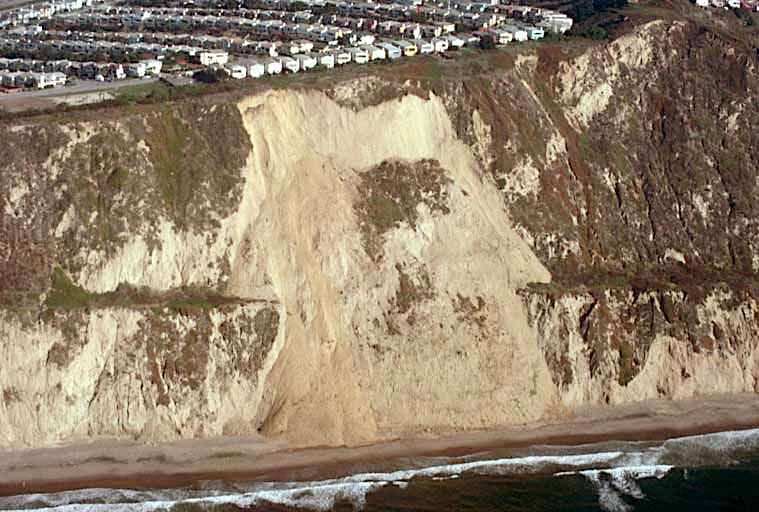 A cliffside with partial material, like sand and dirt, falling down to the beach below.