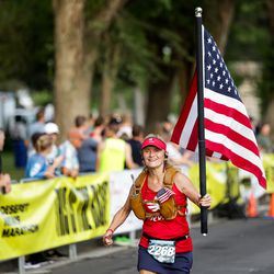 Kandi Rasmussen carries an American flag while nearing the end of the Deseret News 10K at Liberty Park in Salt Lake City on Friday, July 23, 2021.