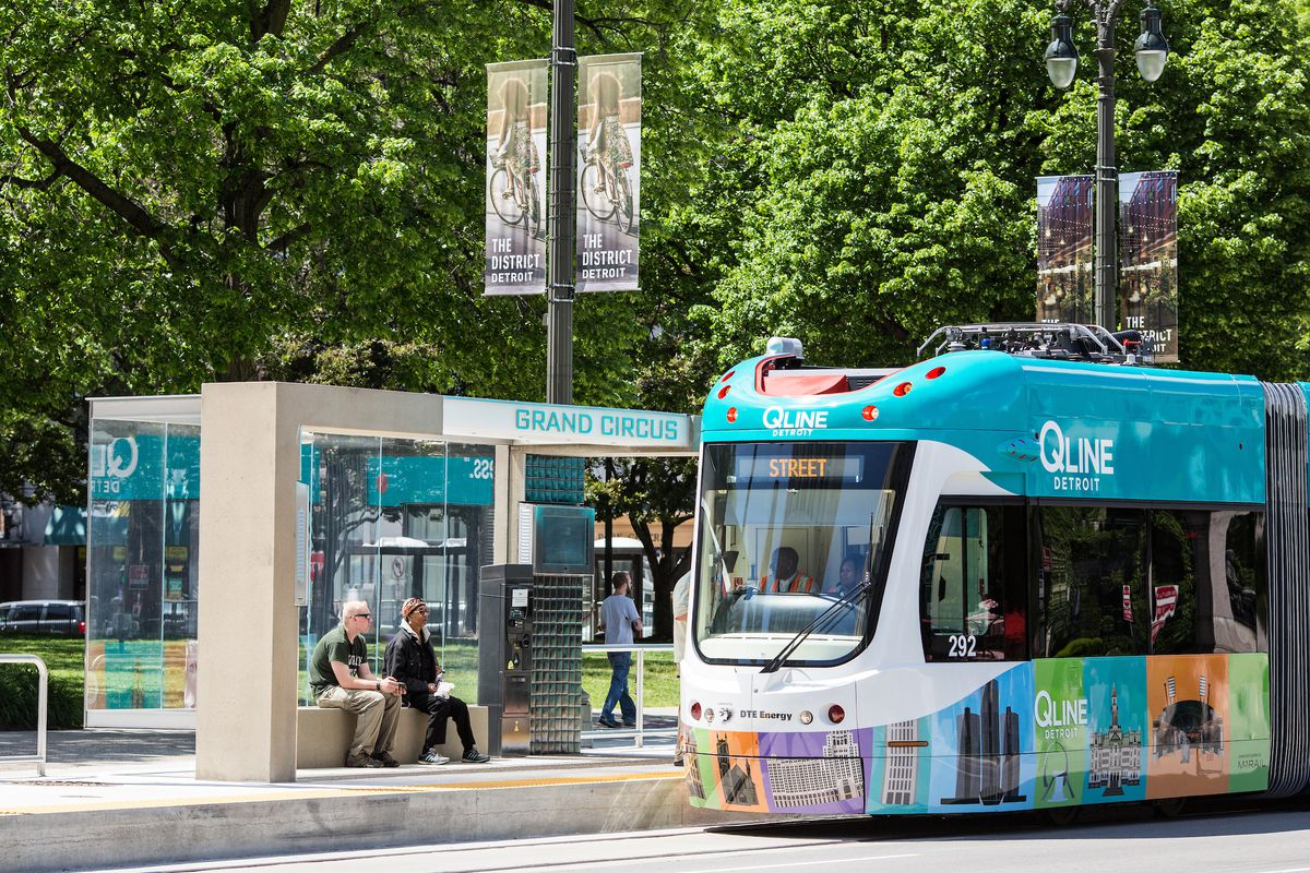 """A colorful streetcar pulls into a stop with the words """"Grand Circus"""" at the top."""