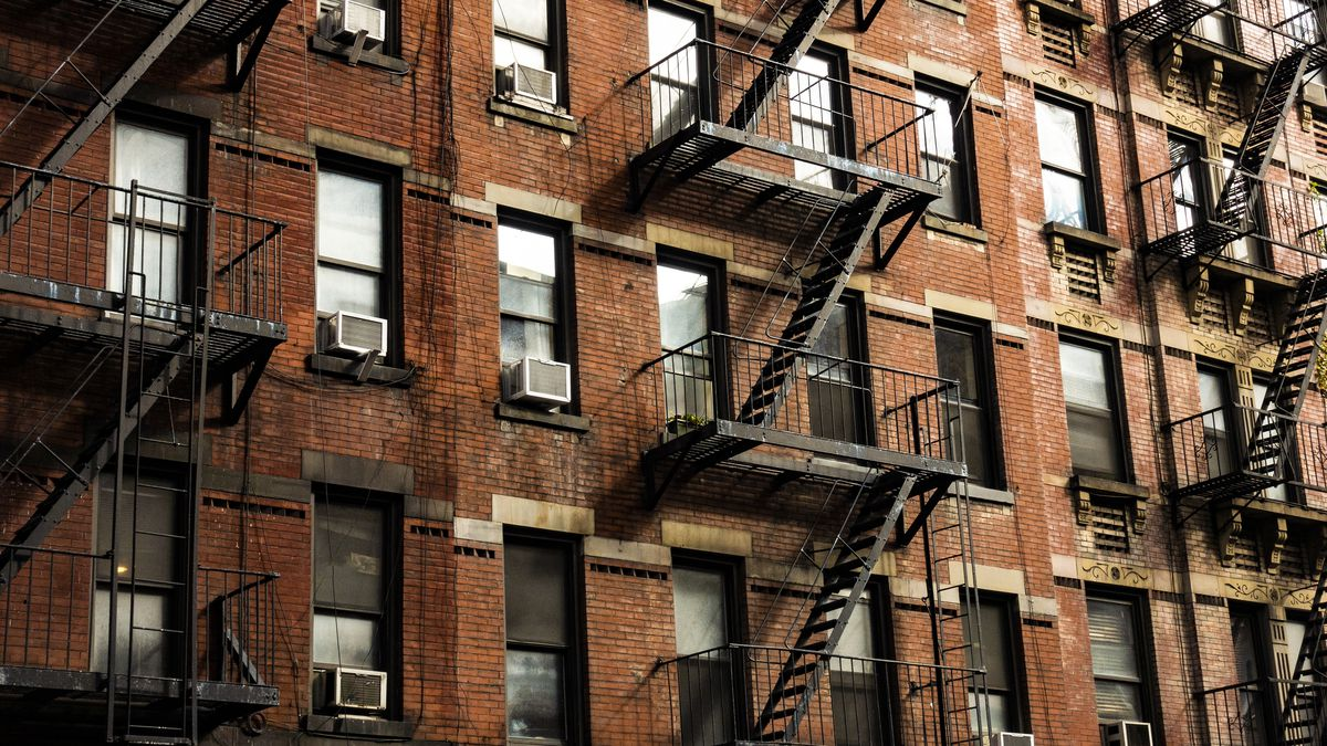 A row of red-brick apartment buildings on a block in Manhattan.