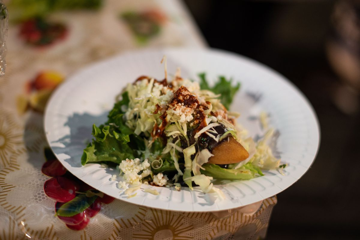 A finished molote, Oaxacan street snack, covered with sauce and lettuce.
