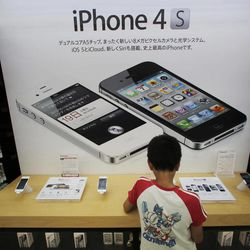 FILE-In this Friday, Aug. 31, 2012 file photo, a boy checks an iPhone at an Apple booth at an electronic store in Tokyo. Millions of people will likely buy new iPhones after Apple's expected announcement of a new model on Wednesday, Sept. 12, 2012. The new phones would join some 244 million iPhones already sold since the first one launched in 2007. Some have been lost, some stolen and some are still in use. But it's fair to say that millions of iPhones are languishing in desk drawers or gathering dust.