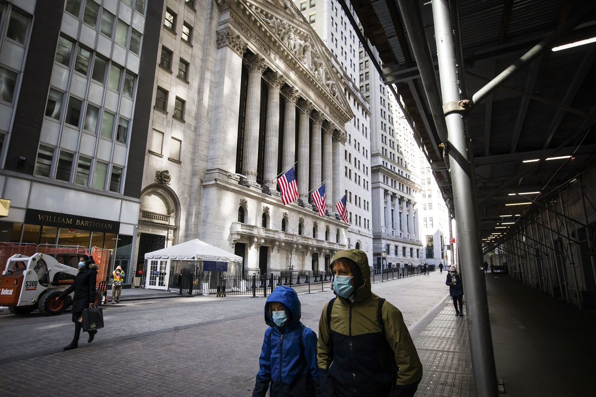 A few people walk past the New York Stock Exchange building on Wall Street.