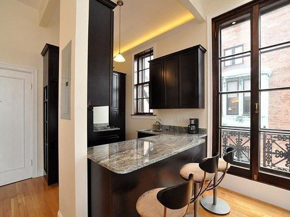 An open kitchen with the corner with stools at the counter.