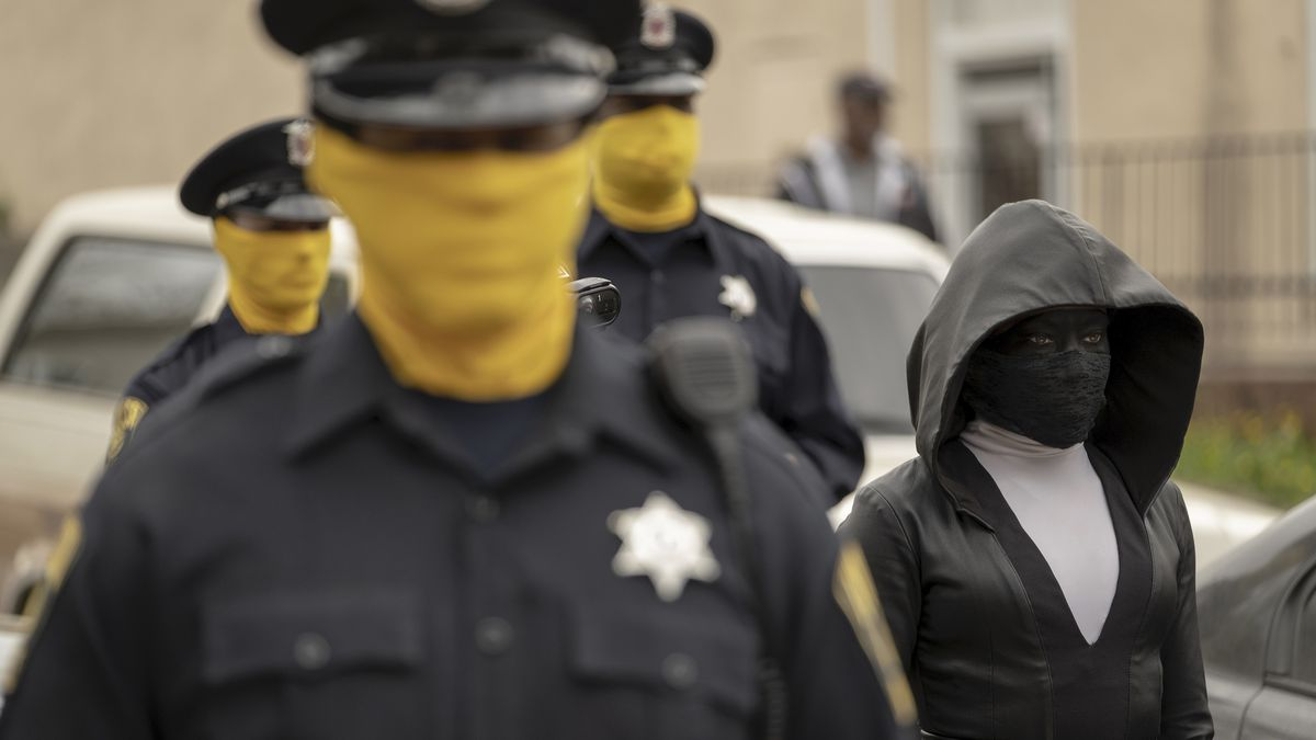 three cops with yellow masks accompany Sister Night on a sting