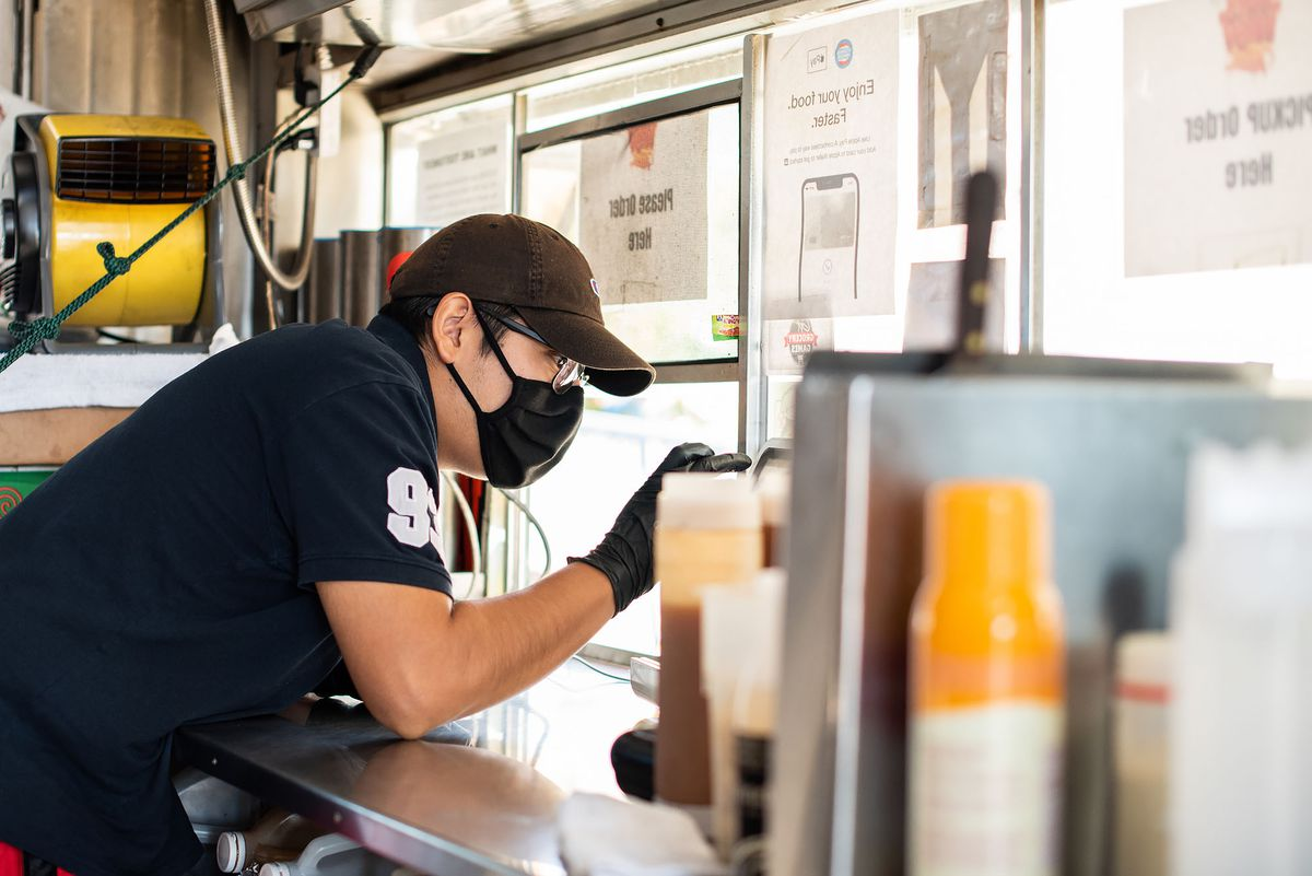 Worker at Triple Threat Truck takes orders at window