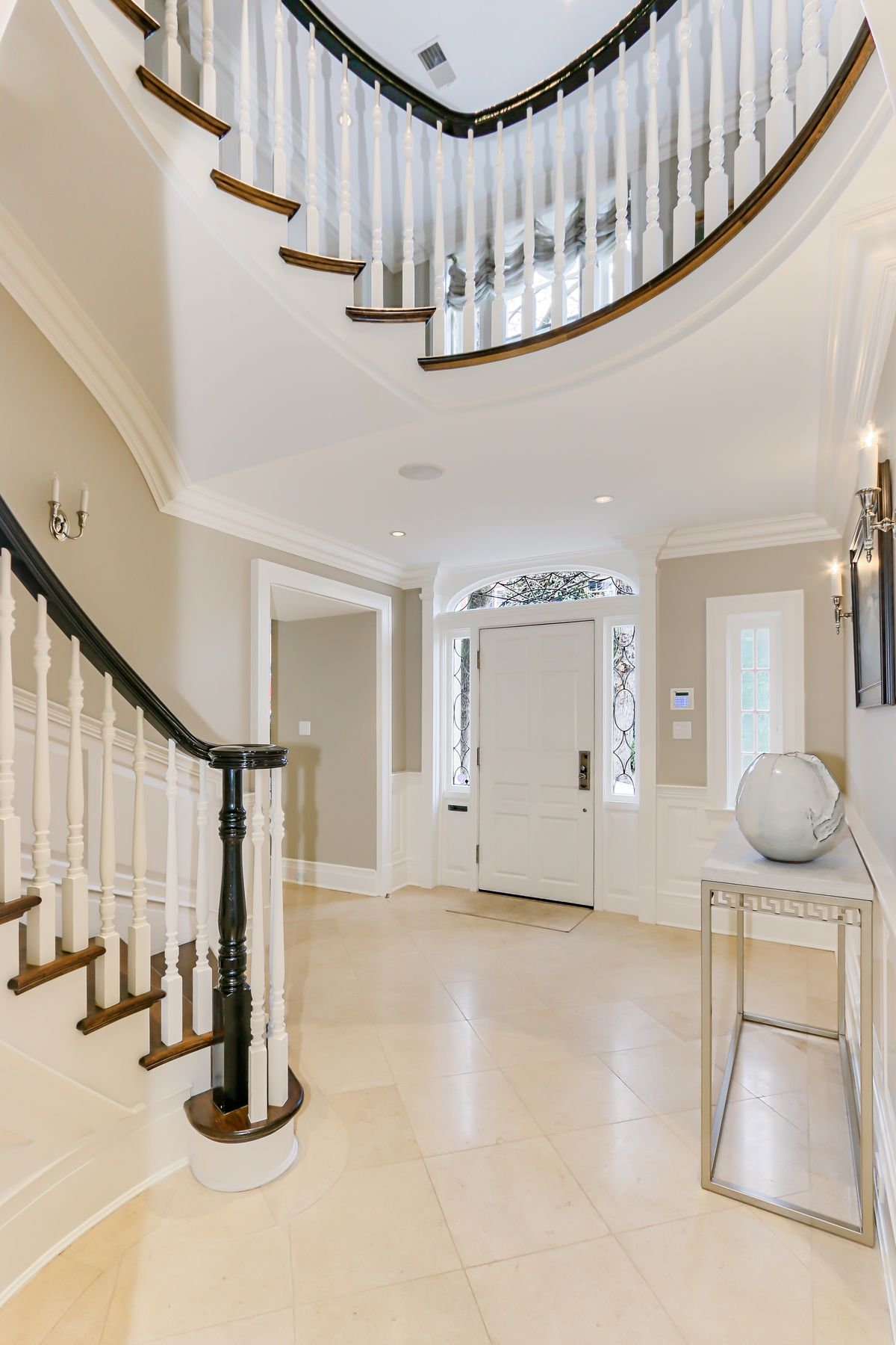 Entryway for a house featuring white walls and stairs.