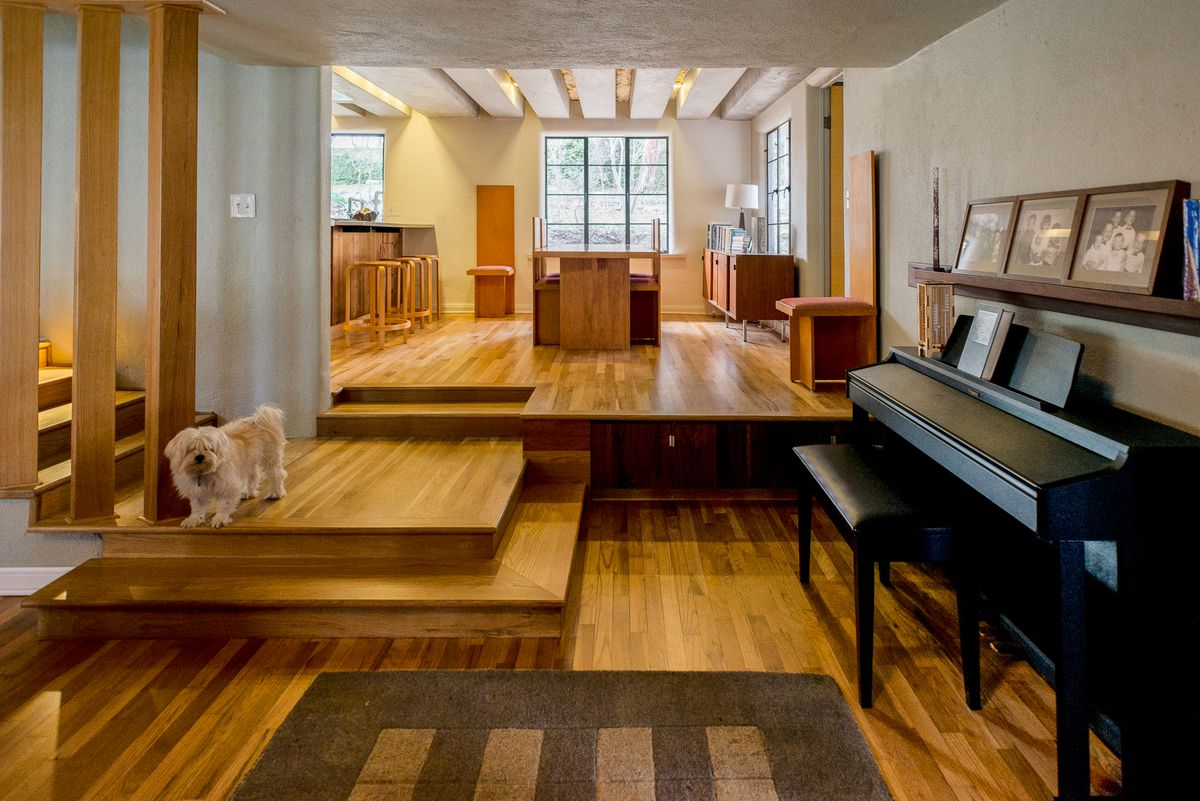 Updated 1955 home interior in minimalist-leaning style with wood floor and features, built-in furniture, piano