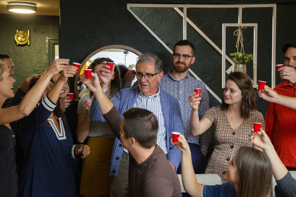 A family raises cups for a toast in a living room