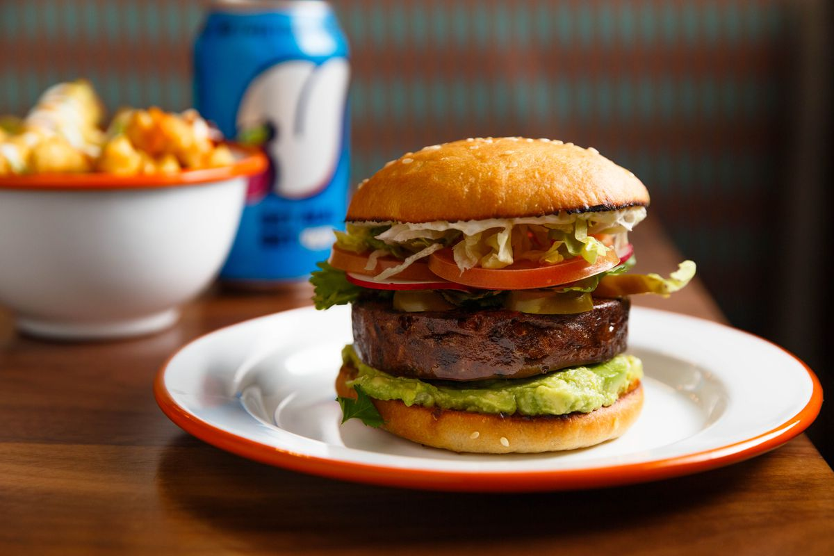 A green swath of guacamole sits underneath a vegan burger, while lettuce, tomatoes, and jalapenos sit on top