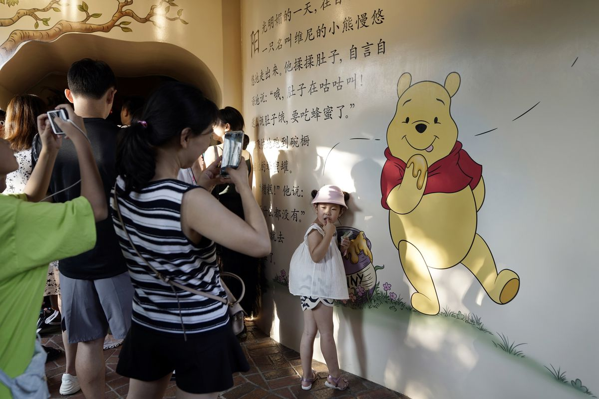 """A child poses for photos near a mural depicting Winnie the Pooh in Shanghai, China, Wednesday, Aug. 8, 2018. Marc Forster's """"Christopher Robin"""" the movie which stars Ewan McGregor as a grown-up Christopher Robin reunited with the beloved characters of the"""
