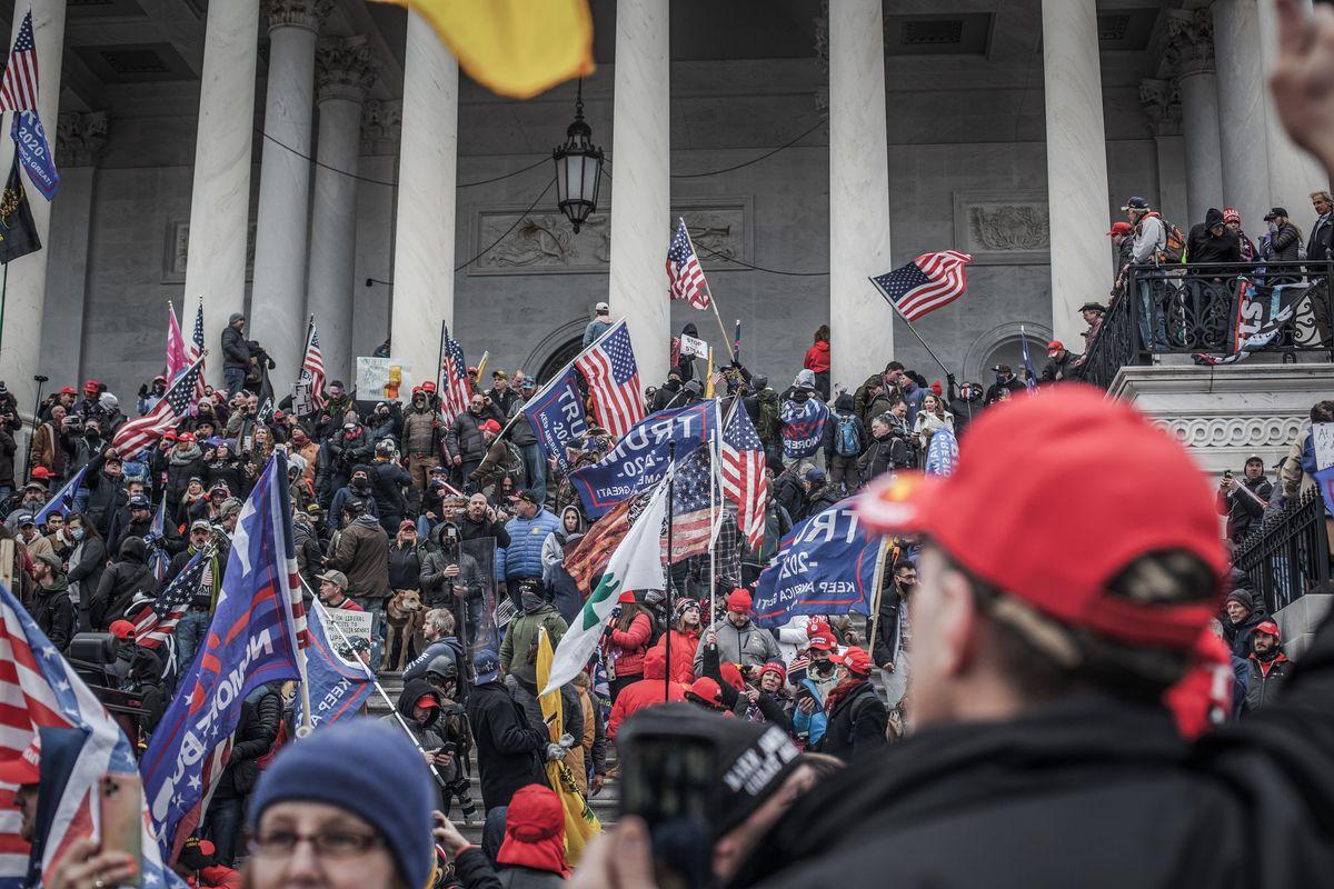 A mass of people cover the Capitol steps and the spaces between its columns; many have on red MAGA hats; still more wave blue flags bearing Trump's name in white.