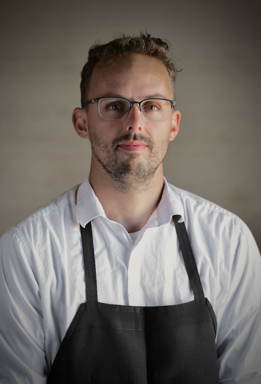 Chef William Eick wearing glasses and an apron.