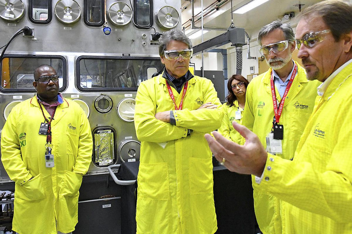 FILE- In this May 10, 2017, file photo, U.S. Secretary of Energy Rick Perry, second from left, accompanied by Laboratory Director Charlie McMillan, second from right, learns about capabilities at the Los Alamos National Laboratory's Plutonium Facility, fr