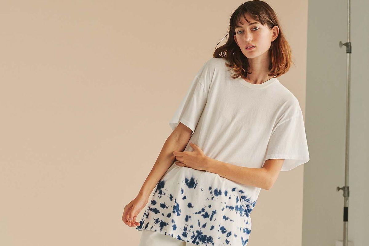 Model against seamless in tie dye shirt