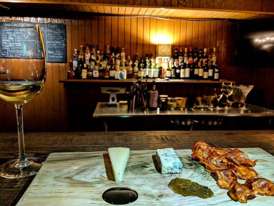 A bar with old-fashioned, wood-paneled walls, shelves of booze, and a chalkboard with a menu written on it. A glass of wine and a cheese and charcuterie board sit on the bar.