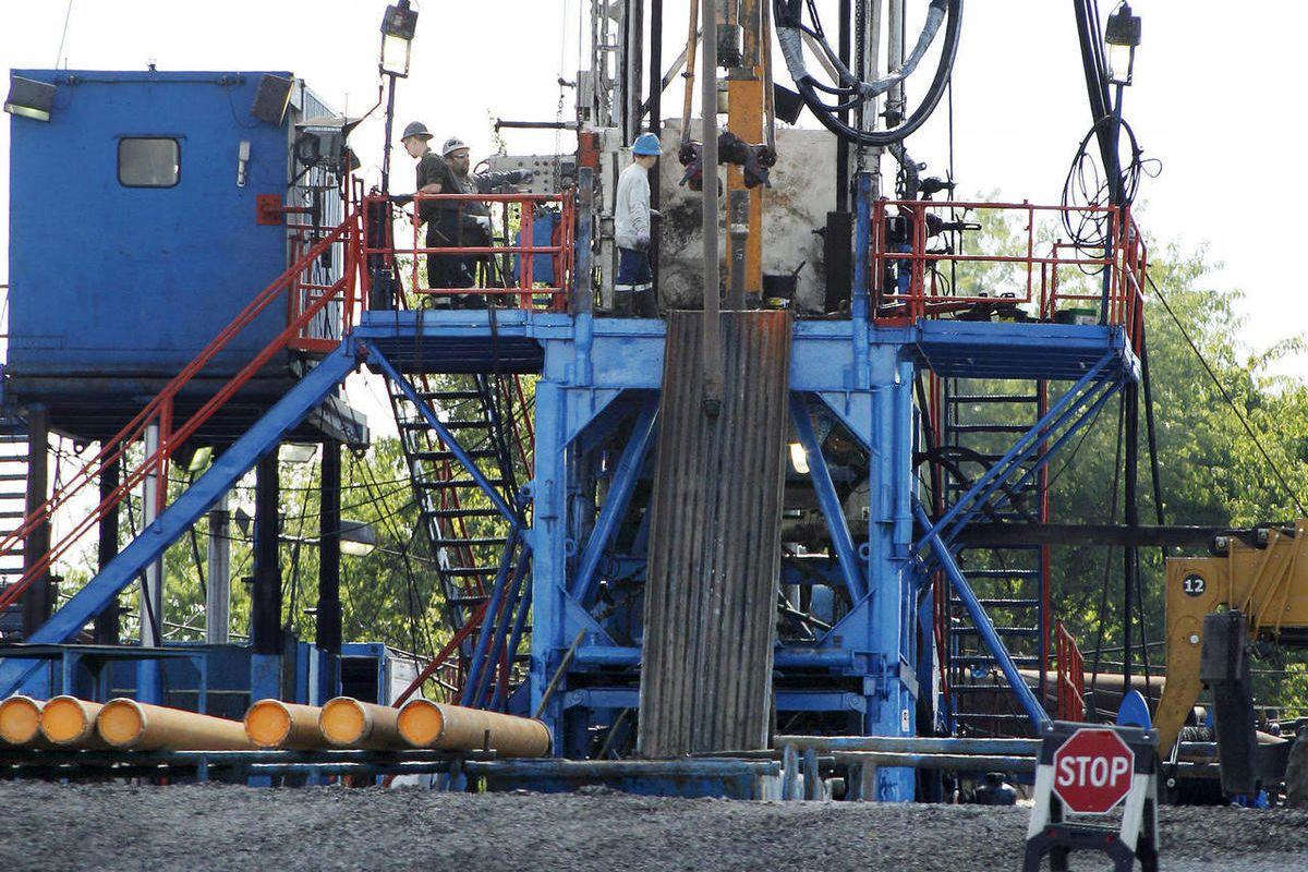 In this June 25, 2012 photo, a crew works on a drilling rig at a well site for shale-based natural gas in Zelienople, Pa. A new fee on gas drilling has generated millions of dollars more in revenue than first projected, but other major gas-producing state