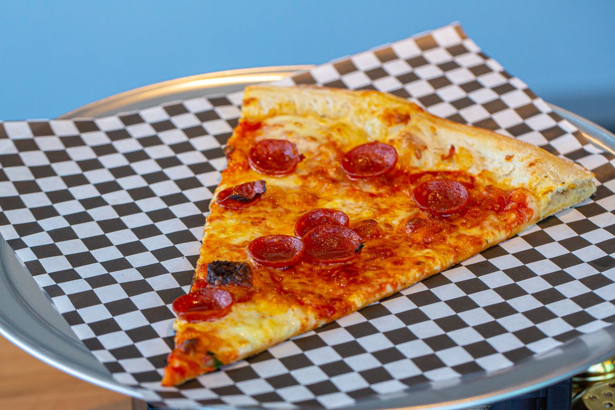 A slice of pepperoni pizza atop checkerboard tissue paper on a round pizza tin