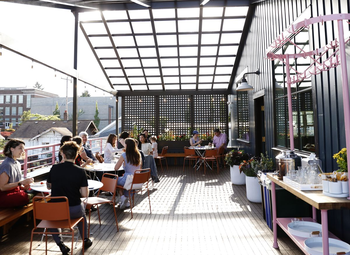 A rooftop deck at a Seattle cafe with customers sitting at tables, a pink railing, and a pink-accented servers' station to the right