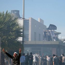 Protesters wave a flag while standing atop the security post of the main entrance to the U.S. embassy in Tunis, Tunisia, Friday, Sept. 14, 2012.  Thousands of demonstrators massed outside the embassy and several were seen climbing the outer wall of the embassy grounds, an Associated Press reporter on the scene said.