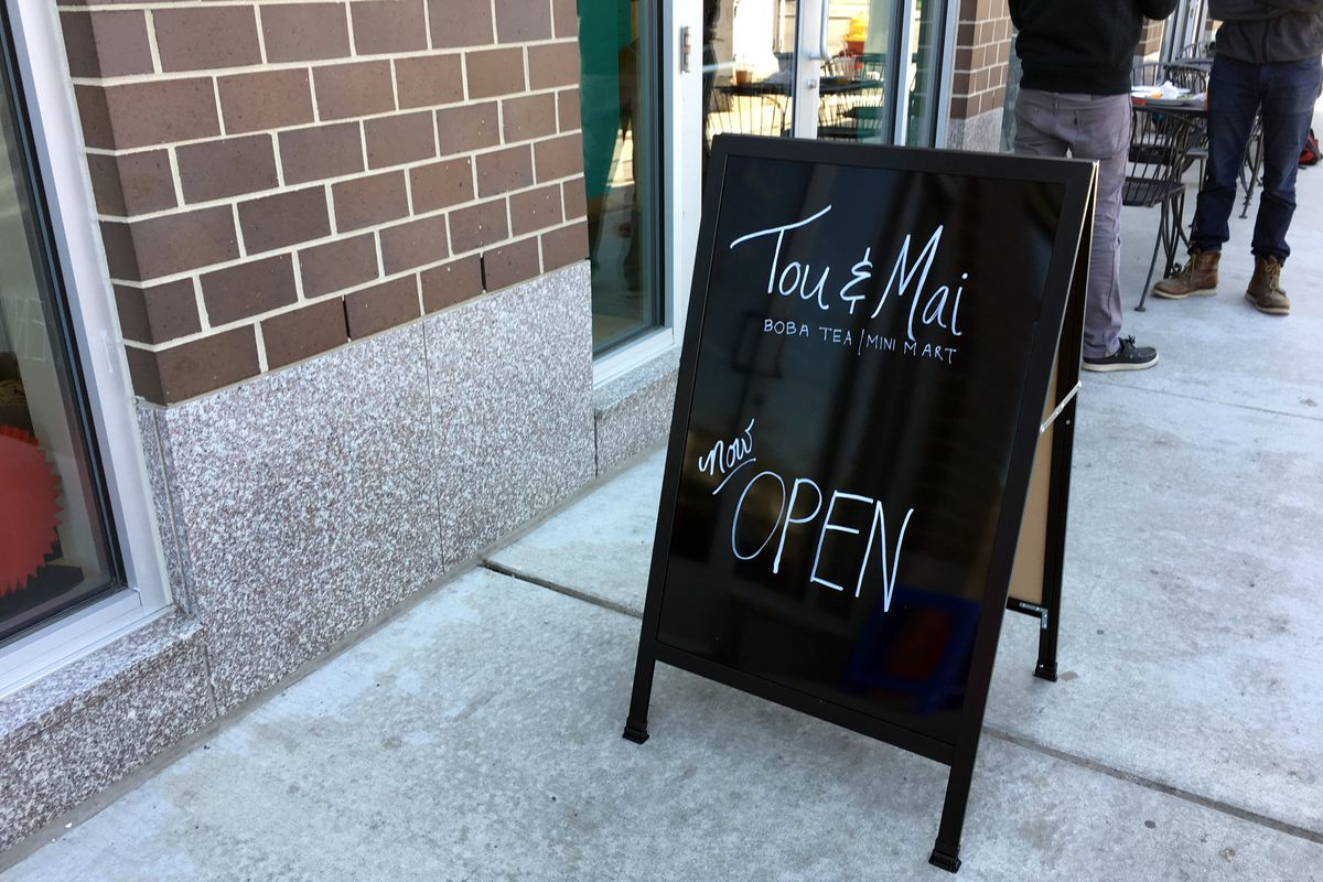 sidewalk sign that says now open